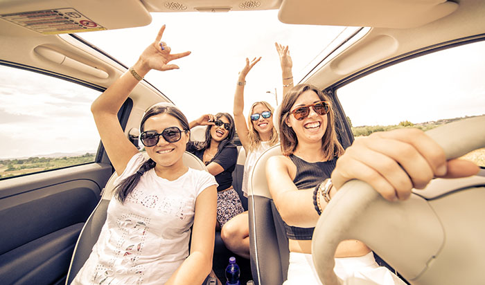 four girls driving in a convertible car and having fun