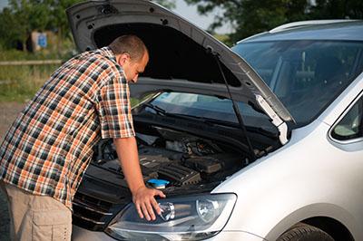 young man checking broken car